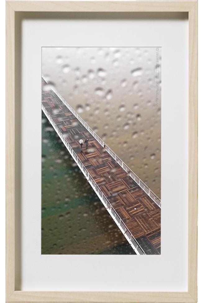 Un couple traverse une passerelle au dessus de l'eau sous la pluie.