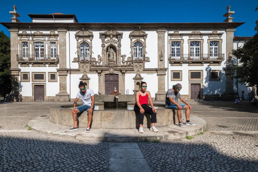 Trois jeunes posent assis sur la fontaine les yeux bandés.Derrière eux la mairie de Guimaraes. Photo pour l'exposition Guimaraes, Aqui Nasceu Portugal de Vincent Aglietti et Vincenzo Cirillo.