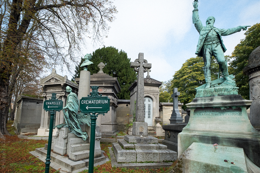 Carrefour du cimetière du Père Lachaise,plusieurs statues et poteaux s'interpellent.