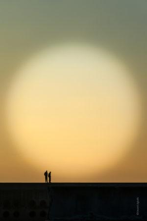 Contre-Jour. Deux hommes sur une jetée observent l'horizon.