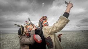 Selfie. Un couple de Carnavaleux sur la plage de Malo les Bains s'embrassant. Un homme photographiant en mode selfie.