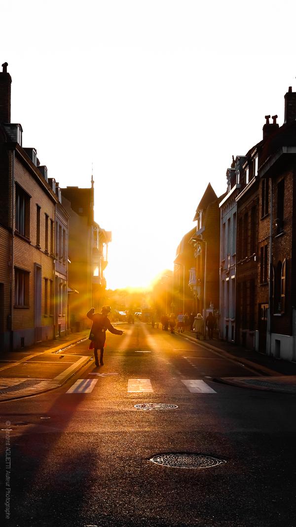 Fin de Carnaval. Un Carnavaleu dansant en traversant la rue. Le soleil.se couche sur Malo.