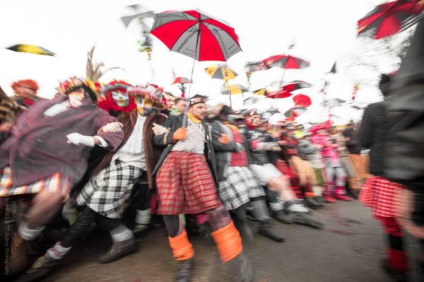 Première Ligne. La première ligne du carnaval tenant leur berguenard et donnant la sensation de s'écrouler dans un flou artistique.