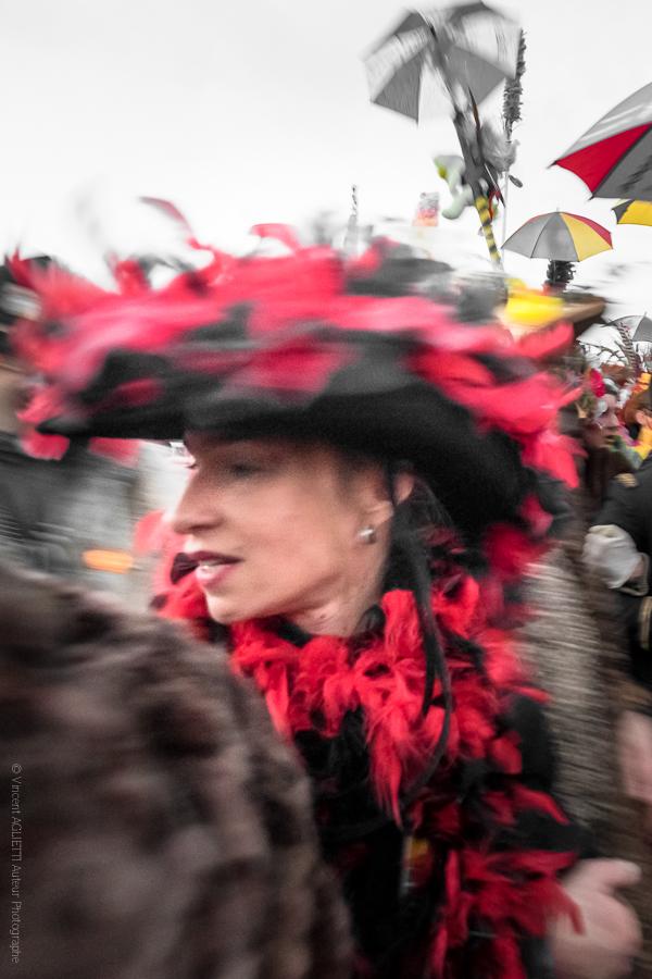 Au Féminin.Une femme coiffée d'un grand chapeau se retournant dans la foule du carnaval..
