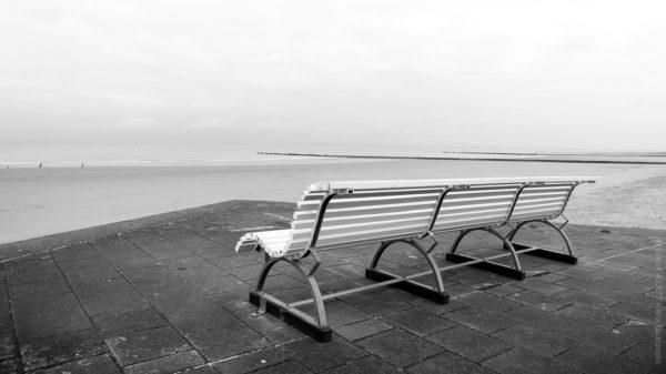Face à la Mer.Un banc vide face a la mer du nord, la plage est vide et le ciel se couvre.