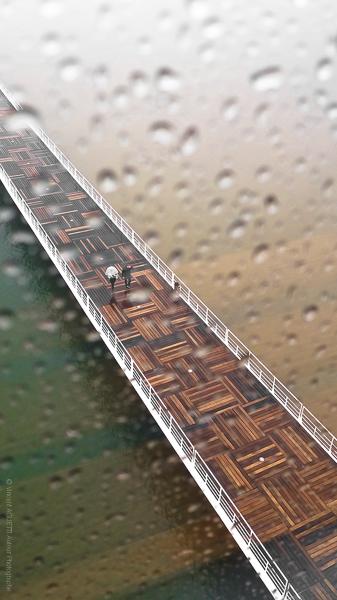Les passagers de la pluie sur une passerelle au dessus du Taje à Lisbonne