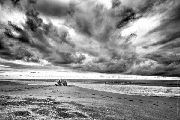Seul au Monde. Un pêcheur solitaire sous un ciel menaçant.