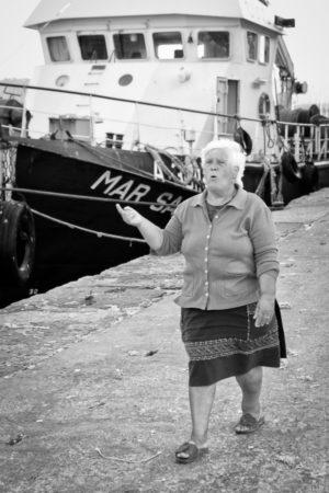 Luiza orchestre le ballet des dockers au rythme de ses gestes et de sa voix.