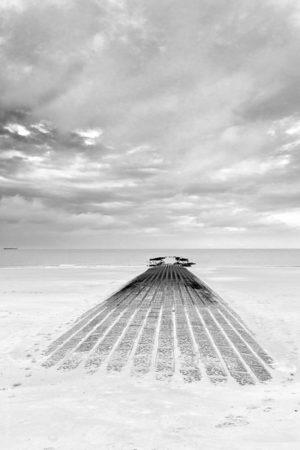 La Jetée Engloutie.Sur la plage de knokke le zoute la mondaine, une jetée rejoint l'horizon sous un ciel orageux.
