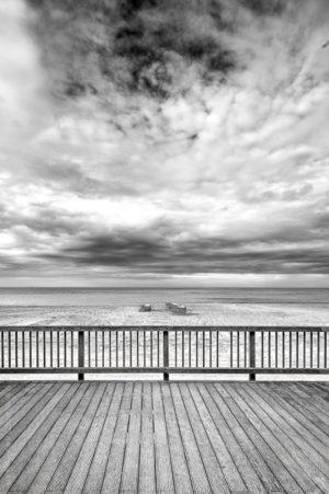 Automne sur Mer.Un terrasse en bois surplombant la plage, sur le sable les paravents et accessoires s'empilent.