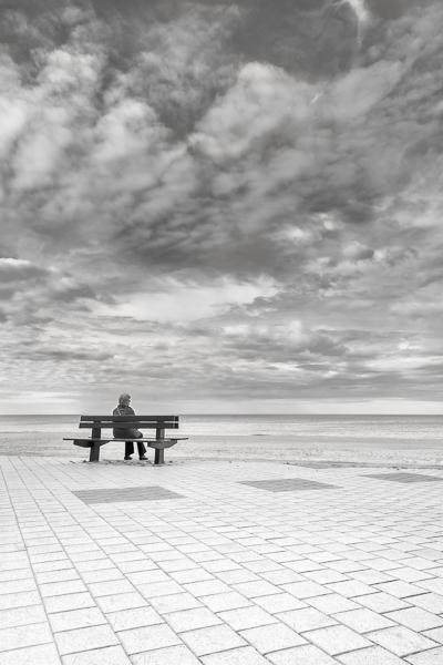 En Attendant. En Belgique a Knokke-Le-Zoute une femme assise sur un banc face a la mer du Nord