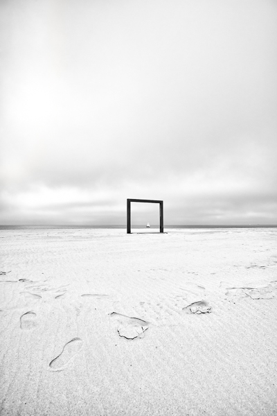 Tableau Flamand. Un portique formant un cadre naturel sur la plage de Knokke, met en valeur un voilier passant au même moment.