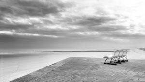 Sans Vis à Vis. Sur les bords de la plage d'Ostende. Un banc vide surplombe la Plage, des traces de pas filent vers la mer. Le ciel est menaçant.