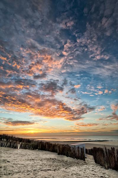 Ciel de Traine.Un coucher de soleil sur la mer du nord, une plage ,une cabine et des canisses contemplent ce spectacle.