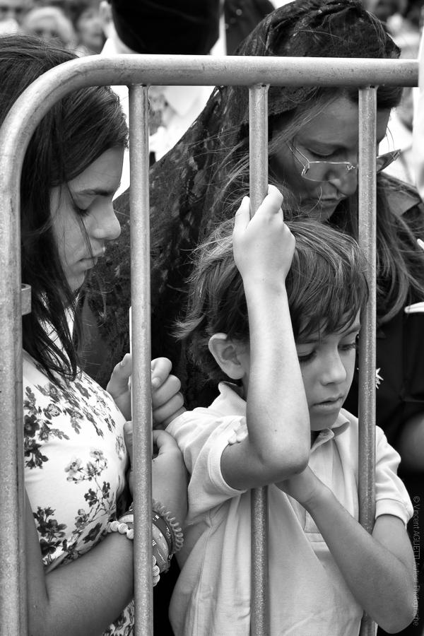 Derrière les Grilles. De Saint-Antoine à Fatima, une famille derrière les barrières prie devant le passage de la procession. .