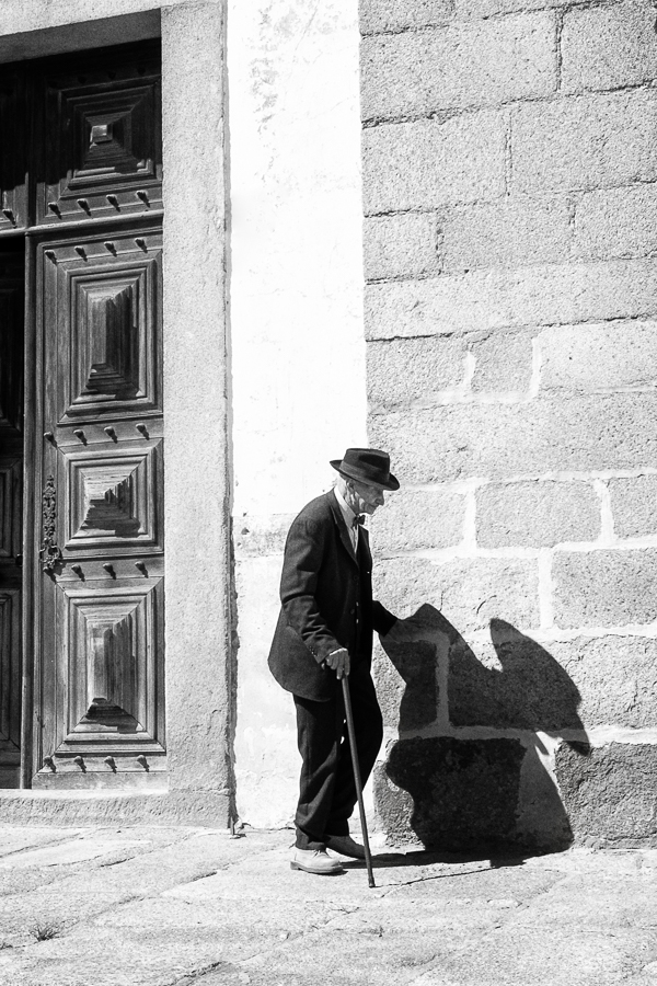 A Petits Pas. Une canne et une ombre accompagnent ce vieux passant d'Evora.
